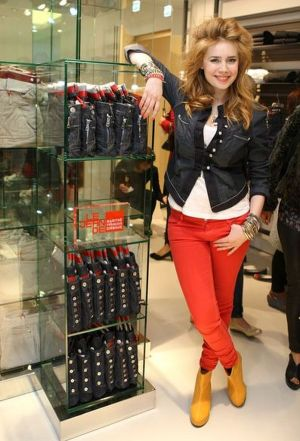 DJane Palina Rojinski in front of a shelf with folded 'ankle signage' denims