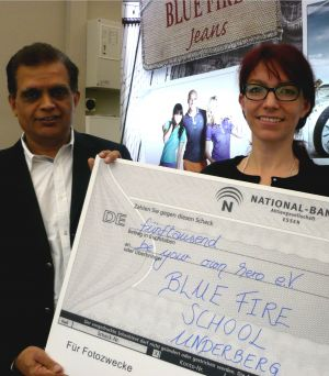 Blue Fire CEO J.Alwani hands over the first cheque to Sandra Wukovich