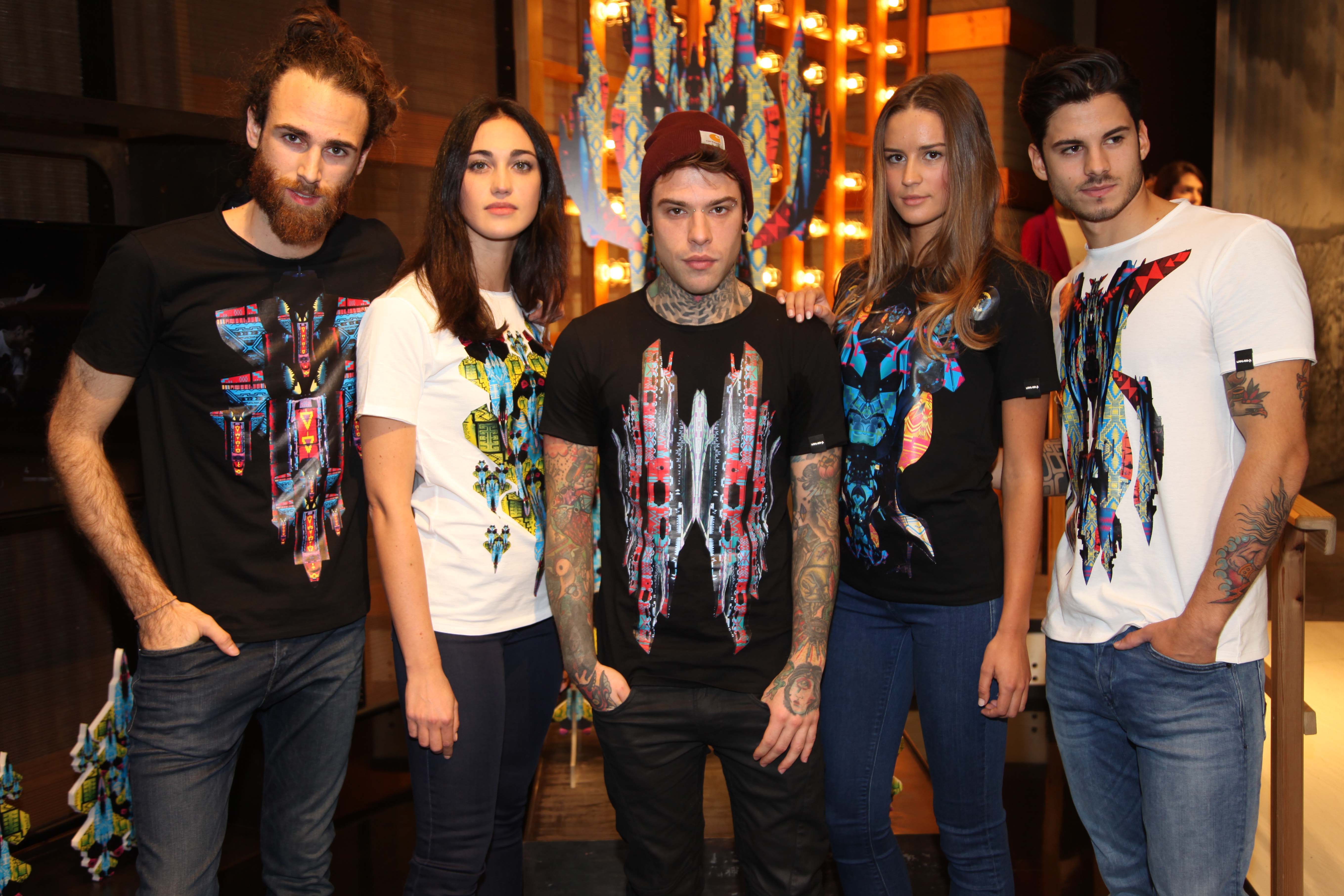 Fedez (center) surrounded by models wearing some of his graphic tees for Replay.