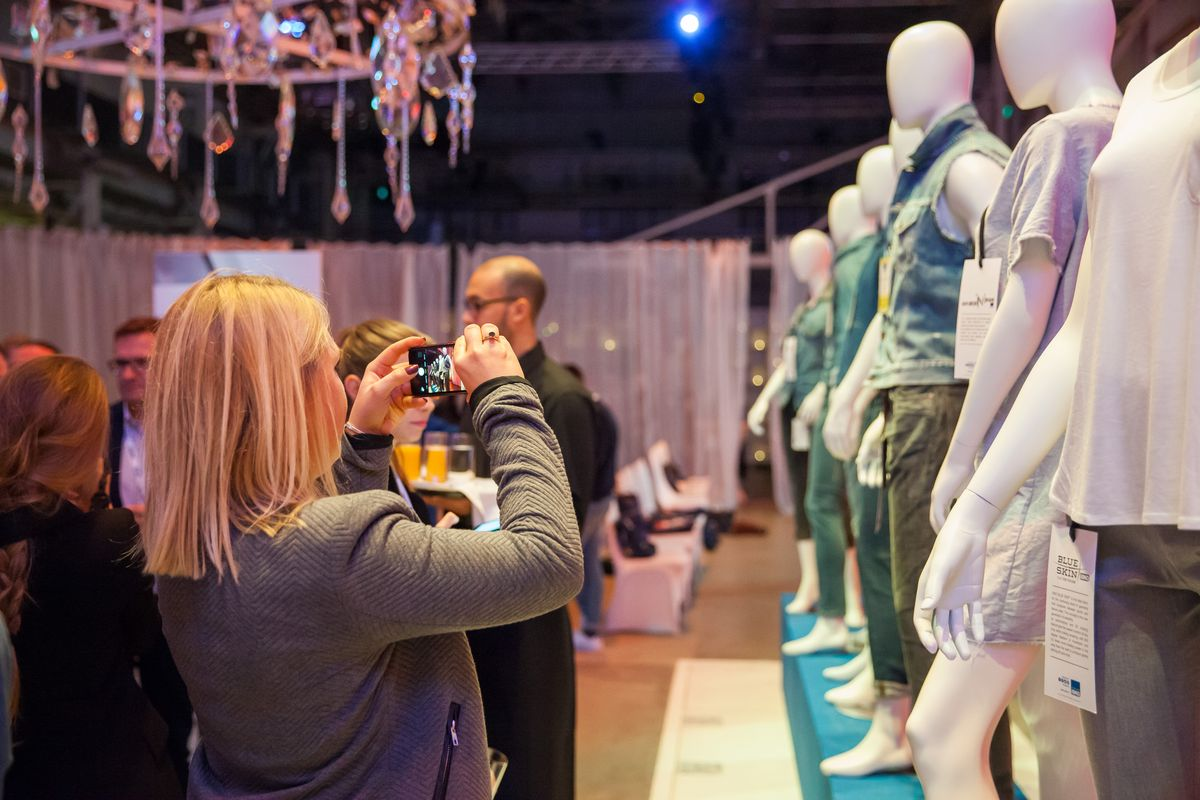 A guest taking pictures of the Isko garments displayed at the event.