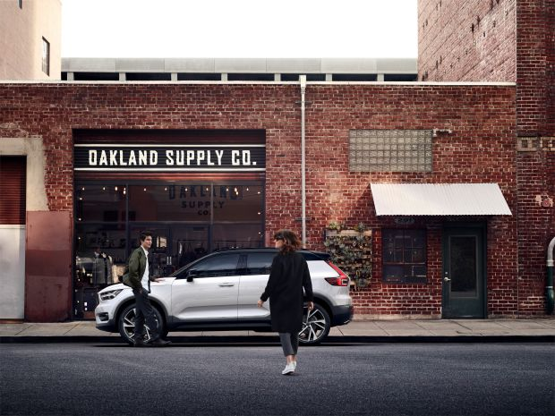 Volvo XC40 compact SUV staged in front of a fashion store.