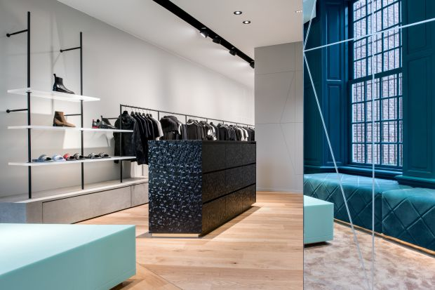 The flagship store also features a turquoise accent wall paired with plush, square seating in the same hue — evidence of the more classic design elements.