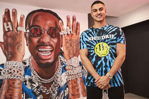Samir Kamani in front of the Quavo mural at the BoohooMan Manchester head office