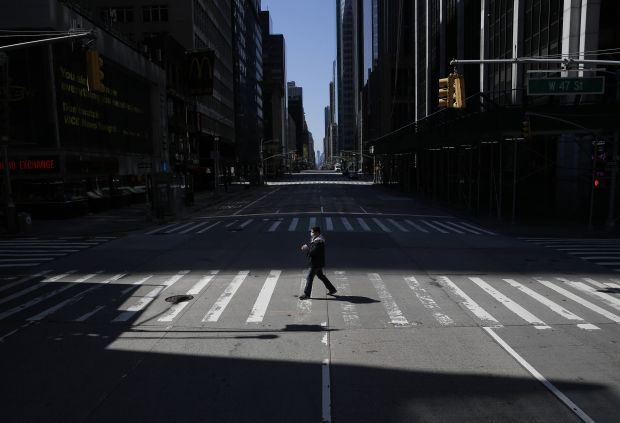 A pedestrian wearing a protective face mask crosses a nearly empty street on 5th Avenue