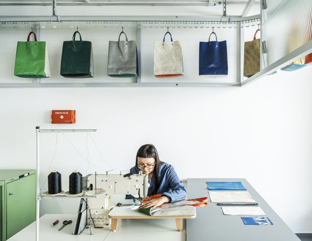 An employee in the shop sews a bag