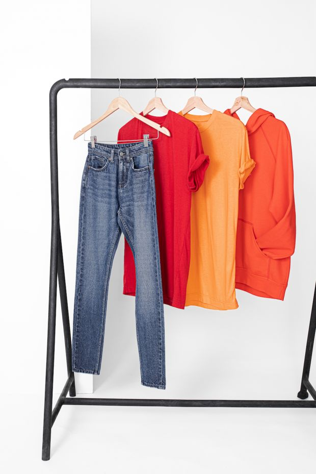 Garments made with Infinited Fiber created from 100% regenerated post-consumer textile waste. From left to right: Jeans 50% Infinited Fiber/50% cotton, red T-shirt 50% Infinited Fiber/50% cotton, orange T-shirt 100% Infinited Fiber, orange hoodie 75% Infinited Fiber/25% cotton.